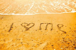I LOVE ME written on the sand of a beach